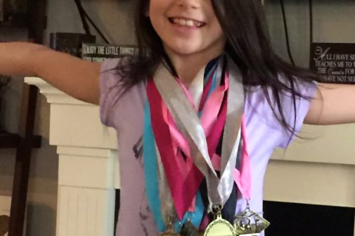 Grace with gymnastics medals from level 3